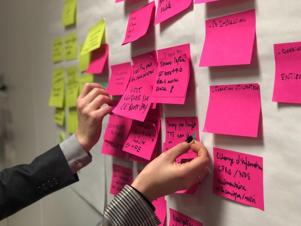 Obrazek przedstawia ścianę z karteczkami.. Zwinne zarządzanie projektami wstęp do Agile.